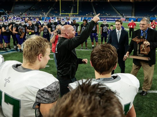 Grand Rapids West Catholic coach Joe Hyland points the direction of the fans as he accepts the trophy for the Division 5 championship at the Ford Field on Saturday, Nov. 25, 2017.