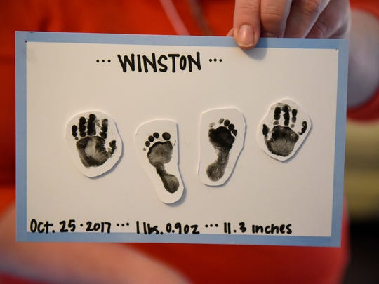 Jenny Borgstrom holds a sign with the handprints and footprints of her son Winston Saturday, Nov. 25, at the St. Cloud Hospital's Neonatal Intensive Care Unit.