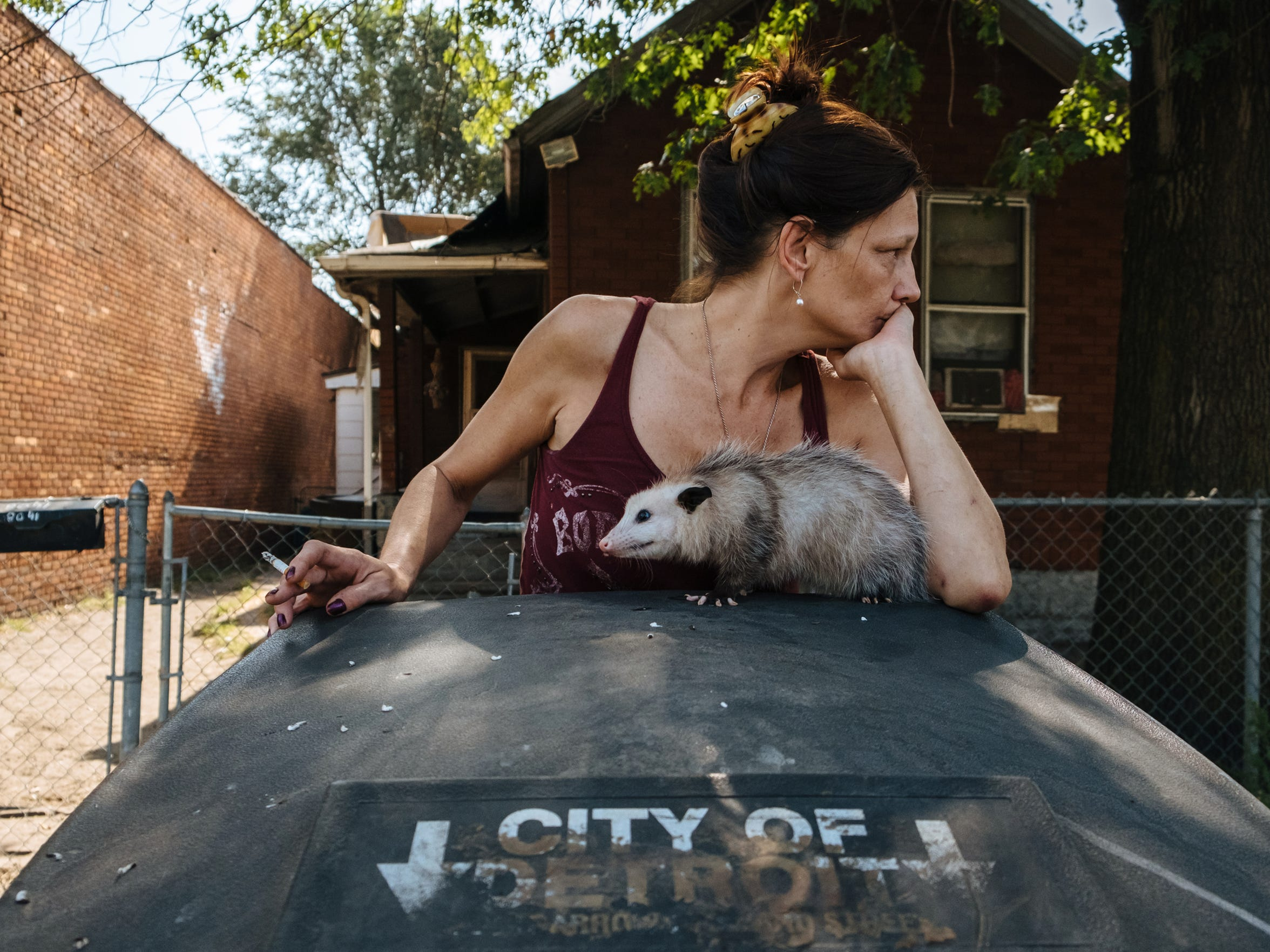 "Fran McCracken, 50, takes a cigarette break as her pet opossum, which she named Samantha, sits atop a trash can in front of her home in Detroit's Delray neighborhood on Sept. 25, 2017. ""My neighborhood is nice,"" she said. ""It's just peaceful down here. You go across the tracks, that's when it gets bad. Yeah, you don't want to go across the tracks when it's nighttime. You find bodies -- girls -- all the time. Like the other day, my brother was driving down the street and they found a girl dead."""