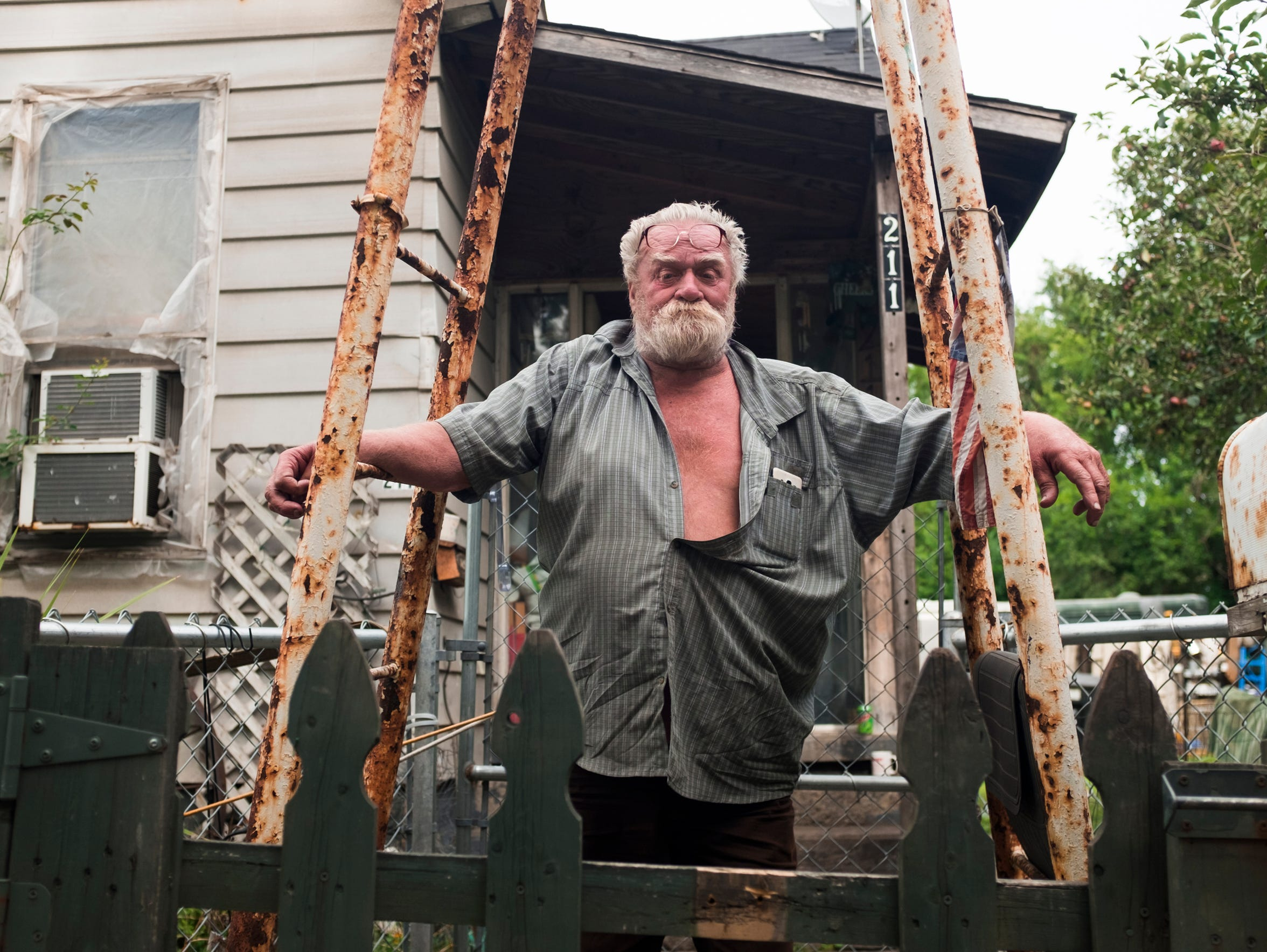 "Mike Donovan, 73, stands at the front gate of his Delray home on Sept. 1, 2017.""We were always used to the industrial neighborhood, so the train and the trucks and stuff, I don't even hear it,"" he said dismissively about the near-constant noise in the neighborhood. ""You just go to sleep."""