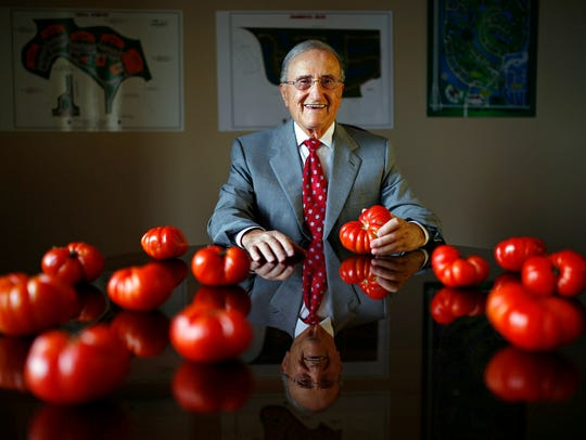 Joe Procacci sits between some of his famous UglyRipe tomatoes and images of his real estate projects in his office Thursday, March 26, 2015, in Naples, Fla. Procacci died Nov. 17, 2017, and his brother Michael died less than a week later.