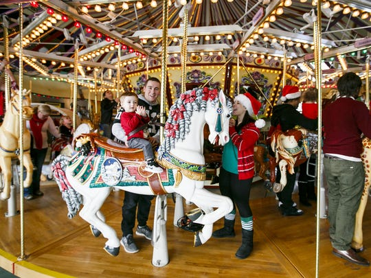 Coleton Walling, 2, claps as he rides the Riverfront Carousel with parents Zach Walling, center, and Nyssa Hicks, right, on Christmas Eve, Saturday, Dec. 24, 2016. The carousel will offer free rides from noon to 4 p.m. on Dec. 25, with a suggested donation to support Marion-Polk County Food Share.