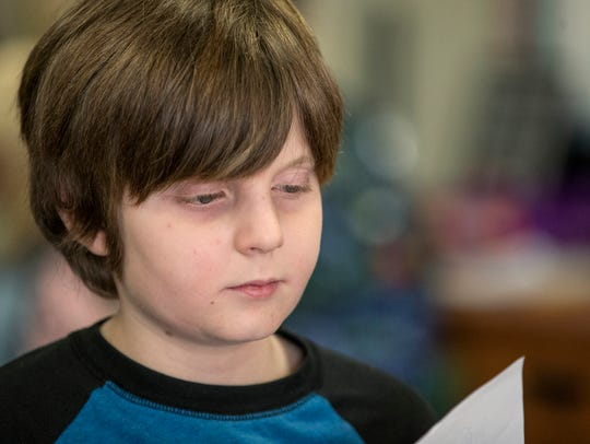 Matthias Vescelus, 9, stashes papers away during class