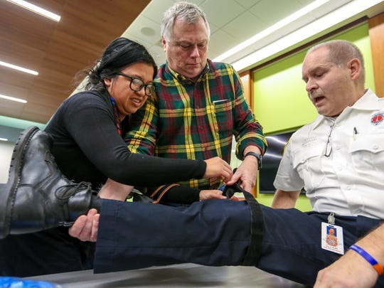 Dana Marquez, 44, of Beverly Hills and Jay Gardner, 58, of Franklin work together to place a tourniquet on instructor James Neufeld of the Farmington Hills Fire Department during a Stop the Bleed class at Beaumont Hospital in Farmington Hills on Saturday, Dec. 9, 2017.