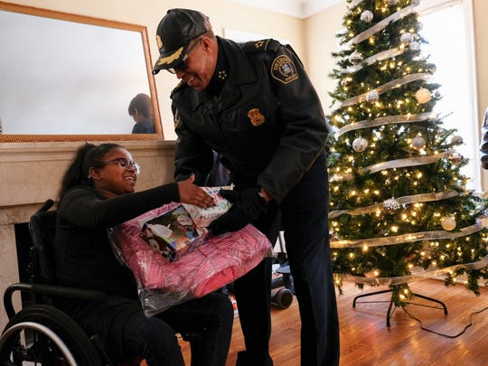 Detroit Police Chief James Craig hands Christmas gifts to India Williams, 10, of Detroit at her home on Detroit's east side on Thursday December 14, 2017 while bringing items as part of the Sergeant Santa program.  Williams was hit by a stray bullet while riding her bike outside of her house and is paralyzed now from the waist down.