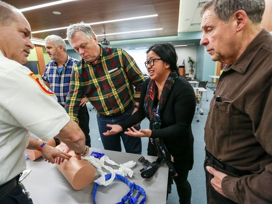 "Instructor James Neufeld demonstrates how to stuff a wound, while Doug Reynolds, 58 of Farmington; Jay Gardner, 58, of Franklin; Dana Marquez, 44, of Beverly Hills and Alan Rayner, 74, of Farmington Hills ask questions and observe, during a ""Stop the Bleed"" class at Beaumont Hospital in Farmington Hills, Mich. on Saturday, Dec. 9, 2017."