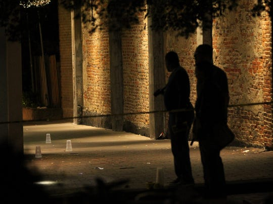 Police officers investigate a shooting near the Sheraton