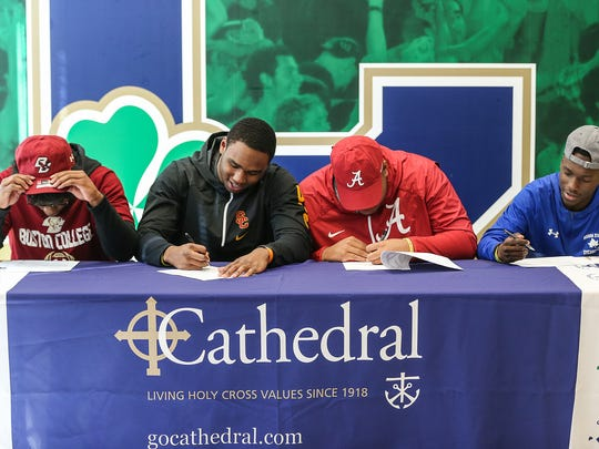 From left, Hugh Davis signs to play football at Boston College, Markese Stepp signs to University of Southern California, Emil Ekiyor signs to Alabama and Daijon Collins signs to Indiana State, at Cathedral High School, Indianapolis, Wednesday, Dec. 20, 2017.