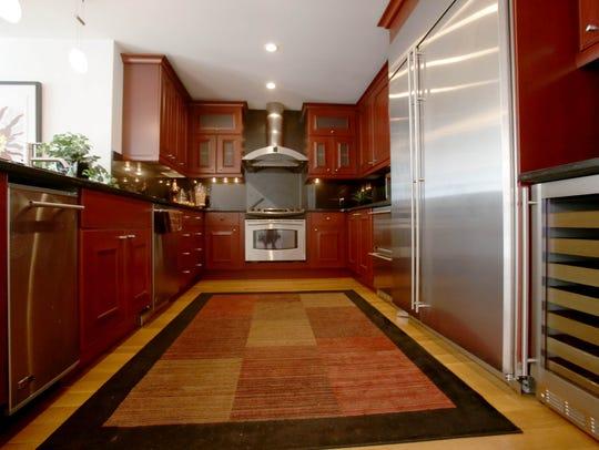 The large kitchen has natural hardwood floors, dark