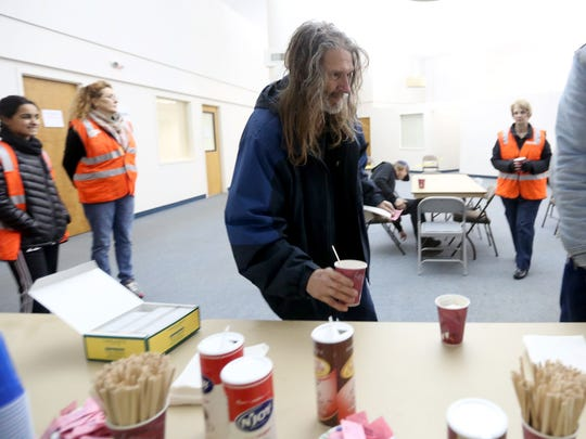 Douglas Dalke, 65, gets a cup of coffee at the opening of the warming shelter at First Christian Church, formerly the site of the Department of Energy, in Salem on Jan. 1, 2017.