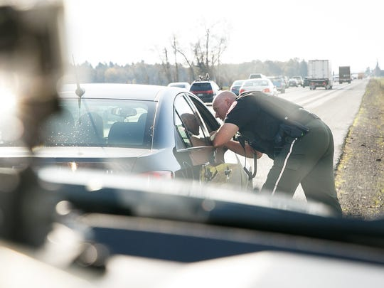 Marion County Sheriff's Office Sgt. Todd Moquin speaks to a driver that he pulled over on the Interstate 5 southbound for reckless driving while he was looking for distracted drivers on Nov. 2, 2017, in Salem.