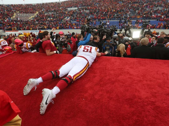 Iowa State Cyclones offensive lineman Julian Good-Jones (51) crawls along the broken stage to touch the Liberty Bowl trophy after the AutoZone Liberty Bowl Saturday, Dec. 30, 2017, in Memphis, Tennessee. ISU defeated Memphis 21-20.