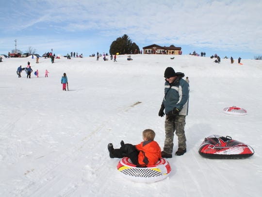 Luka Yakich and his dad, Matthew, finish a trip down the hill during a sledding party at Sussex Village Park in 2016 that included hot chocolate and cookies provided by the park and rec department.