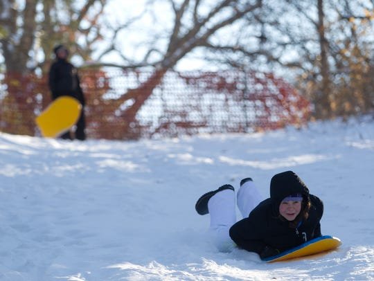 Elena Wilson, 18, sleds down a hill behind Lower City