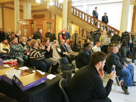 Some members of the crowd applaud State Representative