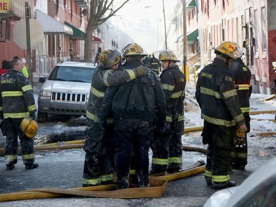 Firefighters embrace as their colleagues battle a row home fire in Philadelphia on Saturday, Jan. 6, 2018. A veteran firefighter was fatally injured when a burning row home collapsed, and he became pinned under the debris, authorities said. A person who lived in the home was also killed. Lt. Matthew LeTourneau, 42, was pulled from the home by fellow firefighters and taken to Temple University hospital. The 11-year veteran was pronounced dead there a short time later.