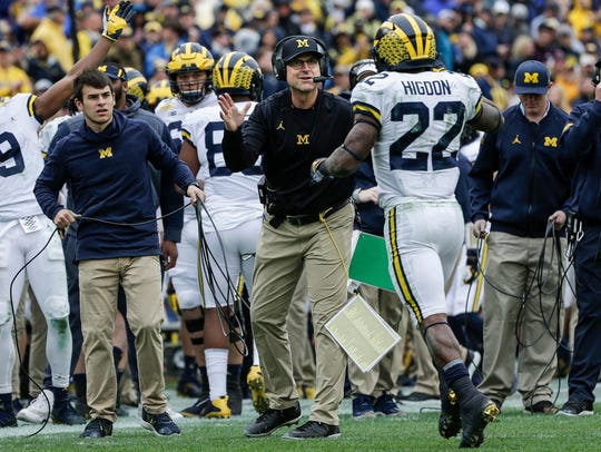 Michigan Wolverines coach Jim Harbaugh high fives running