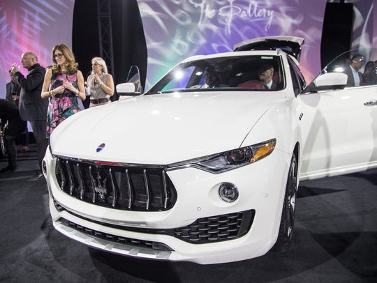 People check out a 2018 Maserati Levante S Granlusso during the Gallery held at Cobo Center in downtown Detroit on Saturday, Jan. 13, 2018. Maserati joins Alfa Romeo, Jeep and Ram as so-called global brands for Fiat Chrysler Automobiles.