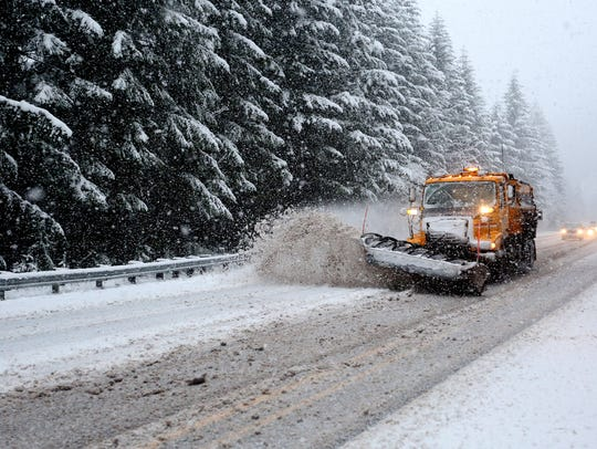 Snow plows run near Detroit Lake, Ore., on Monday,