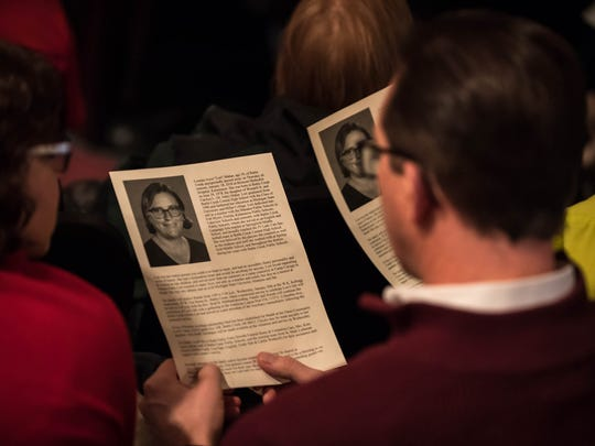 Family and friends read the programs at W.K. Kellogg Auditorium for the memorial for Lori Mahar Wednesday evening.