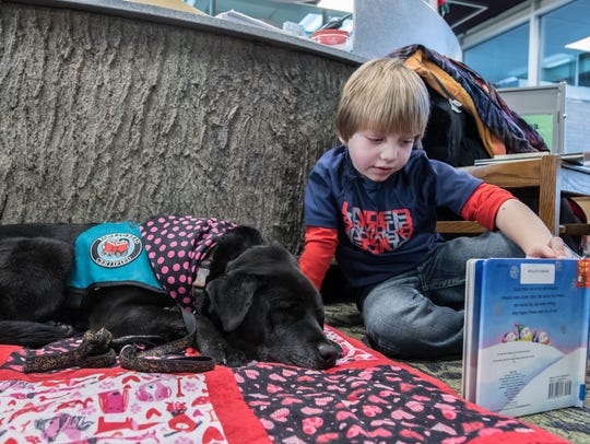 """Six year old Xavier Hoxie reads to Sasha for the """"Paws"""