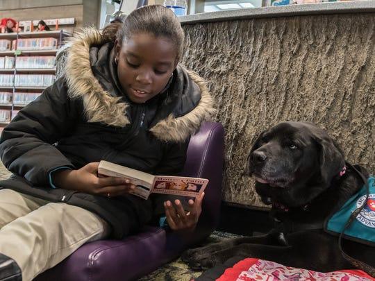 Jha'Niece Turner reads to Sasha, a black lab mix as