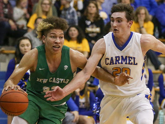 New Castle Trojans forward Mason Gillis (32) tries to shake Carmel Greyhounds Andrew Owens (20) during first half action between the Carmel Greyhounds and the New Castle Trojans at Carmel High School, Carmel, Ind., Saturday, Jan. 27, 2018.