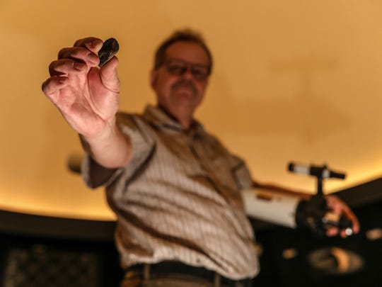 Matt Linke, planetarium manager at the University of Michigan Museum of Natural History, holds up a piece of the Worden meteorite that landed on the roof of a car near Worden, Mich. in 1997.