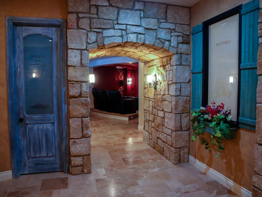 two stone walls hold rustic arched doors with glass