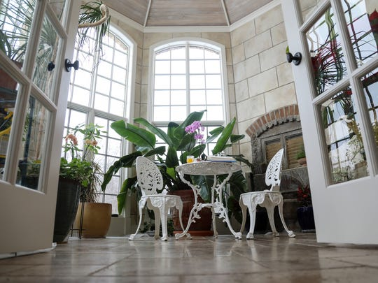 The bay-shaped conservatory — huge windows, stone walls,