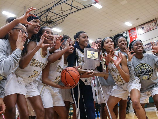 The Warren Central Warriors celebrate with the IHSAA trophy after defeating the North Central Panthers in sectional finals at Lawrence North High School in Indianapolis, Ind., Saturday, Feb. 3, 2018. Warren Central won, 66-54.
