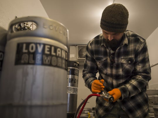Loveland Aleworks head brewer Nick Callaway inspects the lines in the keg room on Tuesday, Feb. 6, 2018, at Loveland Aleworks in Loveland, Colo.