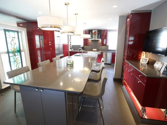 Sleek and striking kitchen has dark red Italian cabinets