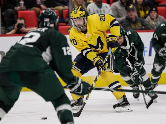 Michigan forward Cooper Marody (20) is defended by Michigan State defenseman Tommy Miller (12) during the second period of Duel in the D at the Little Caesars Arena in Detroit, Saturday, February 10, 2018.