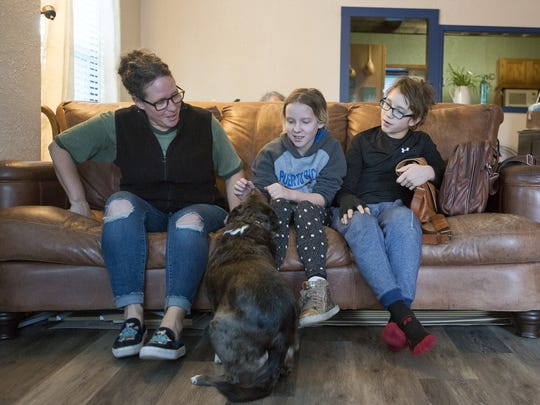 Tara Hildebrand and her children, Ivy and Ranger, make some room on the couch for their dog Huli before posing for a portrait on Friday, Jan. 26, 2018, at the Hildebrand's home in Loveland, Colo.