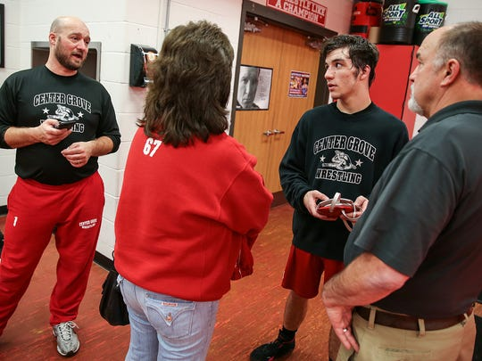 """Coach Cale Hoover, senior wrestler Gleason Mappes and his parents (facing away) Therese and Don Mappes talk after practice at Center Grove High School, Greenwood, Ind., Thursday, Feb. 8, 2018. Wrestling became a Mappes tradition: Don wrestled in high school and Gleason's older brothers Rhett, Sean and Shelby were successful Center Grove wrestlers as well. Therese drives the team bus for away matches and is best known as """"Mama Mappes"""" to Trojans wrestlers."""