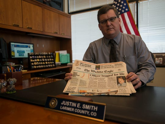 Larimer County Sheriff Justin Smith shows a stack of