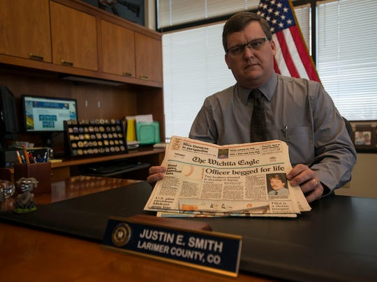 Larimer County Sheriff Justin Smith shows a stack of newspapers with stories written about the slaying of Sedgwick County Sheriff Deputy Christopher C. Willems, as seen on Thursday, Feb. 15, 2018, at the Larimer County Sheriff's Office in Fort Collins, Colo.