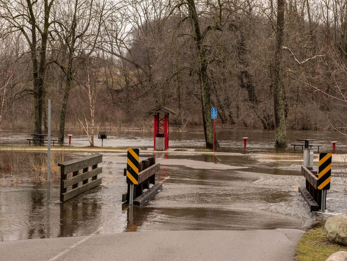Water overflows a road crossing at Historic Bridge