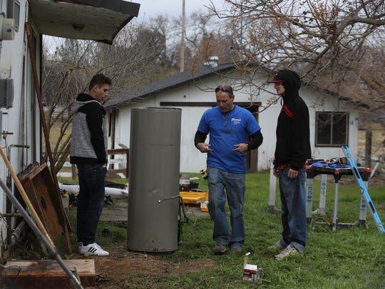 California Heritage Youthbuild Academy students Justin Kelly, left, 16, and Josh Kirby, right, 17 listen as their teacher Carl Hawkins, center, gives instructions to them earlier this year in Anderson. Students in the program were doing some work on a home in Anderson.
