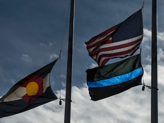 A thin blue line flag flies with the American flag and the Colorado state flag in from of the Fort Collins Police Services building on Thursday, Feb. 15, 2018, in Fort Collins, Colo.