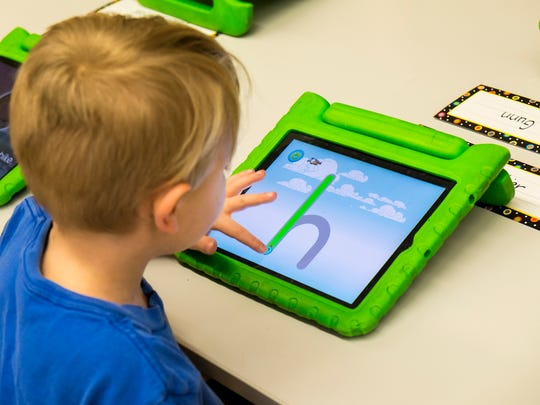 Michigamme Elementary School kindergartener Colton Mitchell  works on a tablet computer during class Feb. 28.