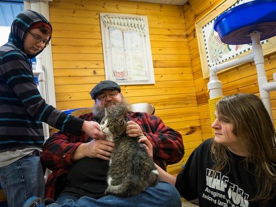 Robert Erdman, center, holds Apollo, a cat available