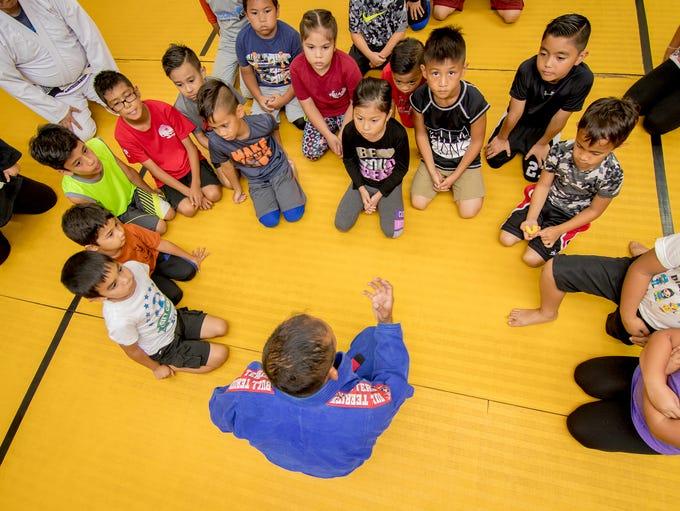 "Jesse ""Spiderman"" Taitano talks to his students at"