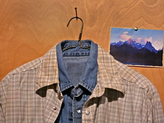 """These two shirts were worn by Heath Ledger, as Ennis Del Mar, and Jake Gyllenhaal, as Jack Twist, in the 2005 Focus Features movie, """"Brokeback Mountain,"""" and they are displayed as in the movie, hanging together on a hanger on nail, with a photo of the mountain, on display in The Reel West exhibit at the Eiteljorg Museum, Thursday, March 1, 2018.  The exhibit, which runs Mar. 3, 2018 to Feb. 3, 2019, looks at """"morality, diversity, and American identity,"""" seen through the Western film genre, Hollywood movies, and television shows."""