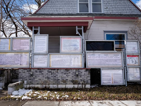 Documents obtained through FOIA requests are displayed on property owned by Philip Risner on 11th Street in Port Huron.