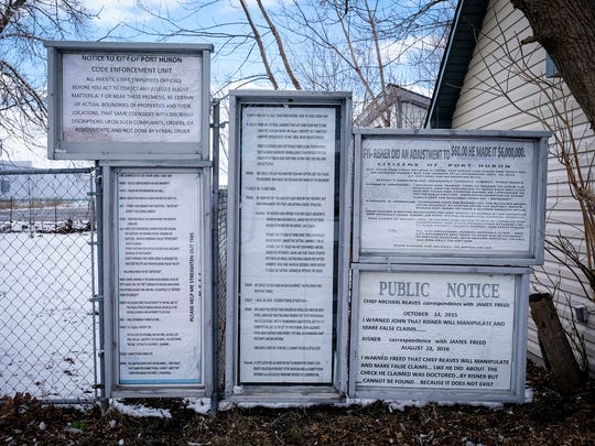 Documents obtained through FOIA requests are displayed on property owned by Philip Risner on 17th Street in Port Huron.