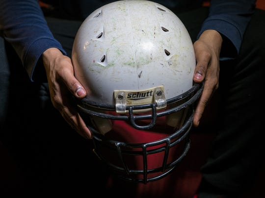 Destin Julian, 19 holds the  practice football helmet he wore while playing Hamady High School at his Flint home, Wednesday, February 28, 2018.