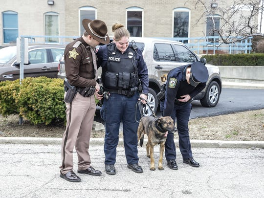 Law enforcement officers William Cline (from left), Taylor Nielsen and Brad Robins stand with Brik on March 5, 2018.