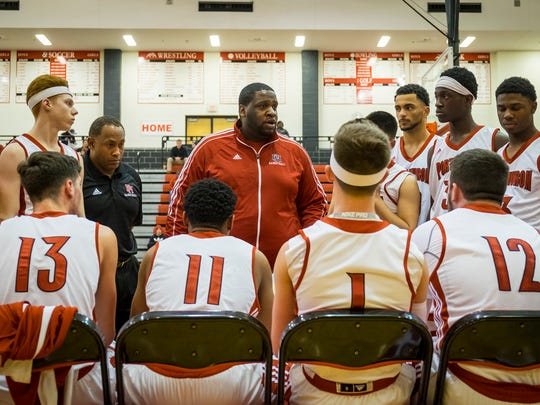 Port Huron High School basketball coach Marion Stewart addresses the team during a time out in the second period of the MHSAA District basketball match against Macomb Dakota High School at Anchor Bay High School March 5.